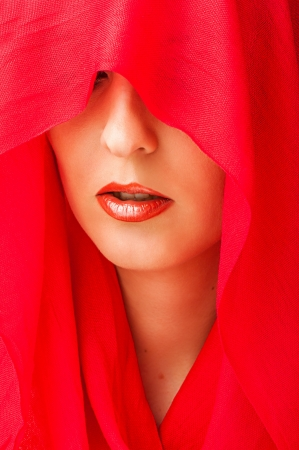 Portrait of sensual woman model with sexy makeup on lips and covered eyes by red  scarf photo