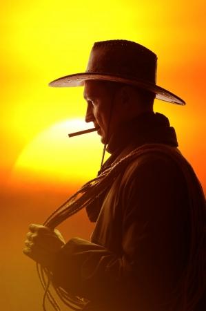 hombre fumando puro: vaquero en sombrero con el cigarro y la silueta lazo Foto de archivo