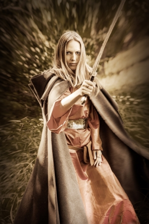 armour: Beautiful blond sexy woman warrior with sword outdoor Stock Photo