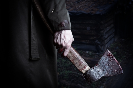downcast: Axe with blood in male hand.  murderer or butcher, halloween theme
