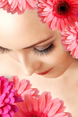 Female beautiful face with false extralong eye lashes close up and gerbera flowers