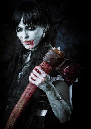 axe: Dead female zombie with bloody axe. Halloween concept Stock Photo