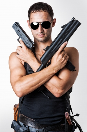 Handsome sexy  military man wearing black fashion sunglasses with automatic and hand gun photo