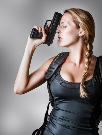Young beautiful sexy blond Woman holding Handgun in hand