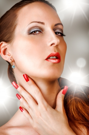 Young woman with long false lashes, fashion red nails and sensual lips - Model posing in studio  photo