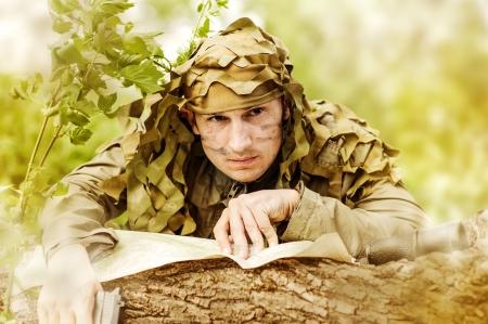 guerilla warfare: Military Camouflaged man in forest with black handgun reading map