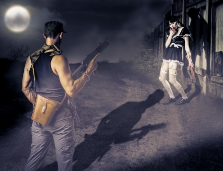 Military man with a gun looking at female zombie with a bloody ax photo