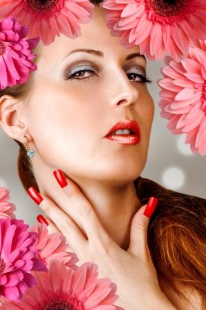 uñas largas: Mujer joven con largas pestañas falsas, las uñas de color rojo de la moda y los labios sensuales con flores