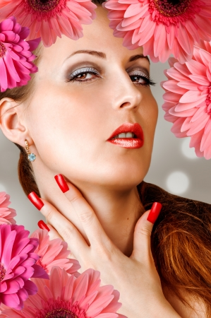 long nails: Young woman with long false lashes, fashion red nails and sensual lips with flowers
