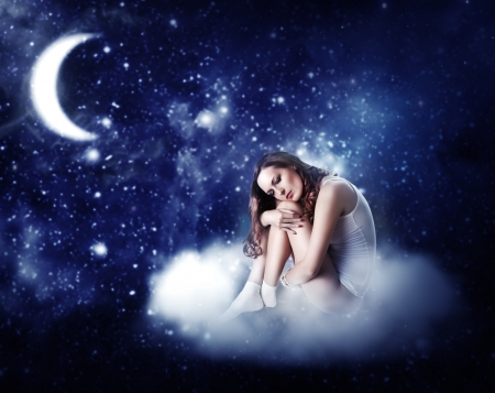 young beautiful woman sleeping on a fairy cloud  in a starry night sky in the moonlight photo