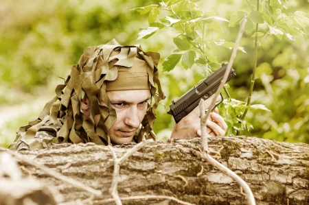 guerilla warfare: Young Camouflaged military man in forest with gun Stock Photo