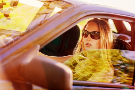 smiling sun: Beautiful young sexy woman wearing sun glasses  in car looking from window on nature background