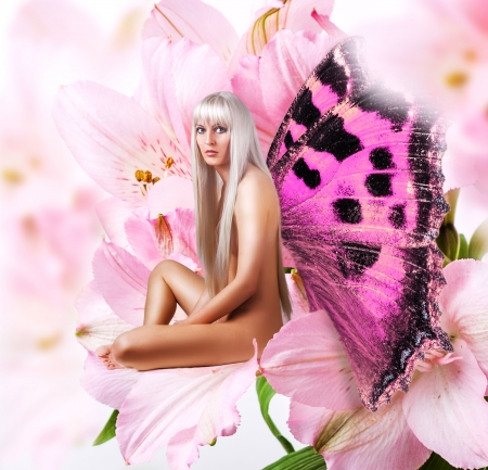 Beautiful sexy woman pixie with wings sitting on a tender pink flower petal  Stock Photo