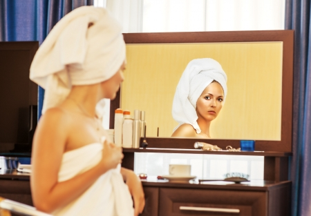 Woman after bath with towel on head looking at the mirror. Focus on reflection photo