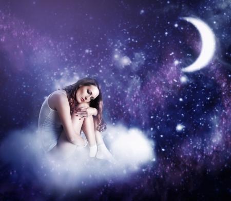 noche estrellada: joven y bella mujer durmiendo en una nube de hadas en un cielo nocturno estrellado en el claro de luna Foto de archivo