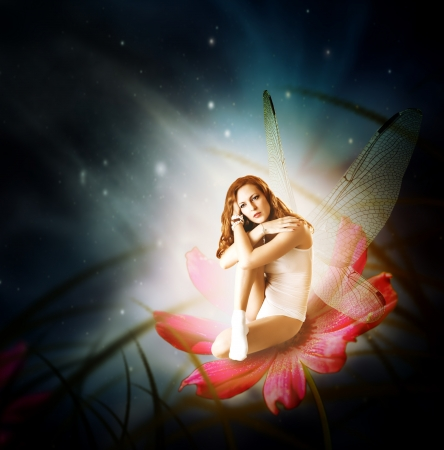 Fantasy. Magical young glowing woman as fairy firefly with wings sitting on flower in moon light photo