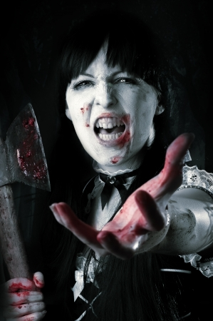 extends: Dead female zombie with bloody axe extends hand to shot. Halloween concept