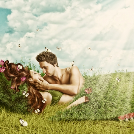 Loving sexy couple  lying in a bed of grass outdoor in summer Stock Photo