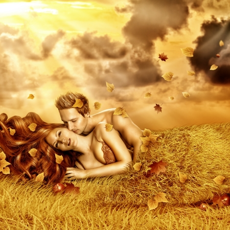 romantic sex: Loving fairy couple  lying in bed of yellow grass, leaves outdoor in autumn sunset Stock Photo