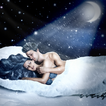 Loving fairy couple lying in bed of white snow outdoor in winter night Stock Photo
