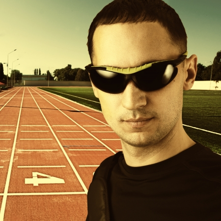 Close-up portrait of a young stylish beautiful man with black sun glasses outdoor at Red treadmill at the stadium photo