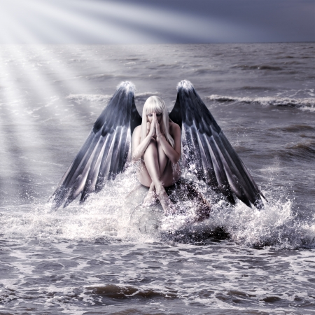 Fantasy portrait of woman with dark angel wings praying while sitting in  spray of  sea during storm photo