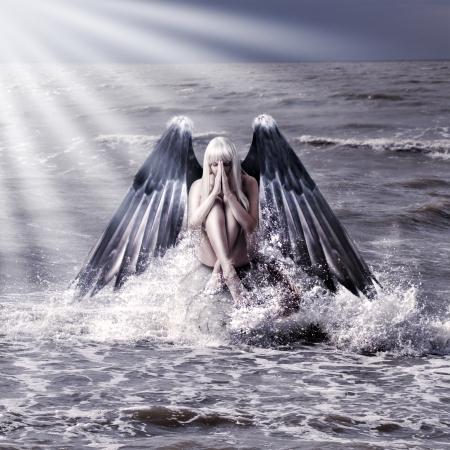 ali angelo: Fantasy ritratto di donna con ali di angelo scuro pregando seduti in spruzzi di mare durante la tempesta