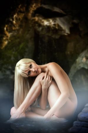 grotte: Beau paysage fantastique avec femme sexy nymphe blonde assise dans le lagon � l'eau