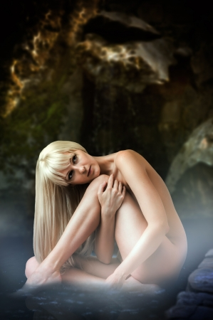 Beautiful fantasy landscape with sexy blond woman nymph sitting in lagoon with water