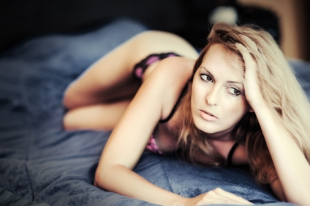 Glamour portrait - sexy beautiful blond woman in lingerie lying on bed photo