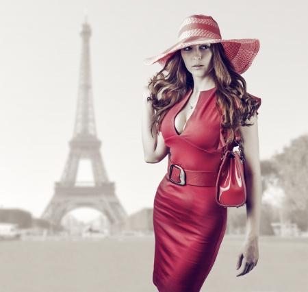 Jonge mooie vrouw dragen van sexy rode jurk, handtas, riem en hoed lopen in Parijs, Frankrijk Stockfoto