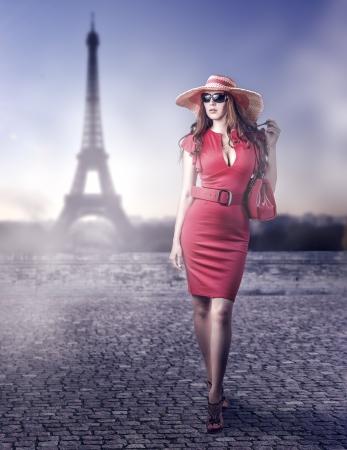 セクシーな赤いドレスを着て、手バッグ、ベルト、パリ、フランスで歩いて帽子身に着けている若い美しい女性