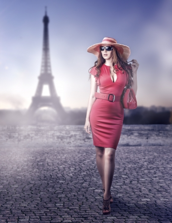 Young beautiful woman wearing sexy red dress, hand bag, belt and hat walking in Paris, France