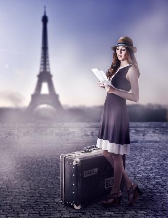 ドレスを着ている茶色のスーツケースと麦わら帽子の若い美しい女性旅行者はパリ、フランスへのガイドを読む 写真素材
