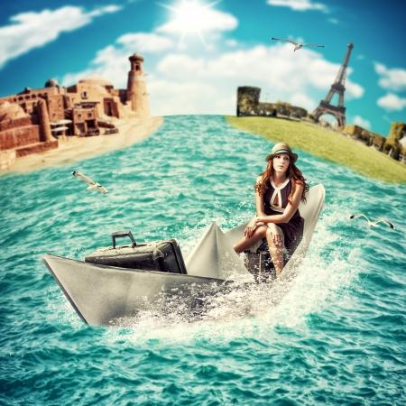 Concepto del recorrido - soñando travesía del mar en todo el mundo la mujer con flotadores equipaje en el barco de papel en el océano Foto de archivo