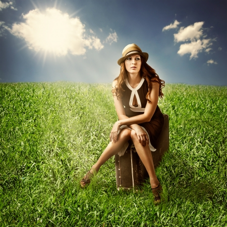 woman traveler sitting on her retro brown suitcase in green meadow