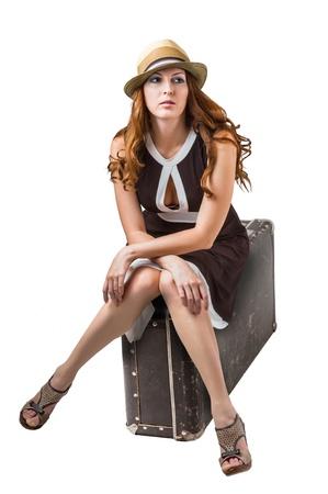 sandalias: Mujer que viaja sentado en su maleta marrón retro en el fondo blanco Foto de archivo
