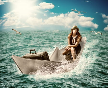 floats: dreaming about sea cruise around the world.Woman with luggage floats on the paper boat on the ocean Stock Photo