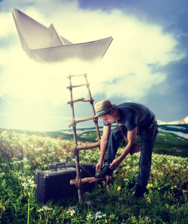 Handsome man with suitcases standing near the ladder to the flying paper boat in the clouds
