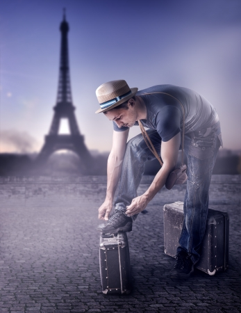 Young handsome casual man Traveler in a straw hat with old brown suitcase wearing dress read guide to Paris, France photo