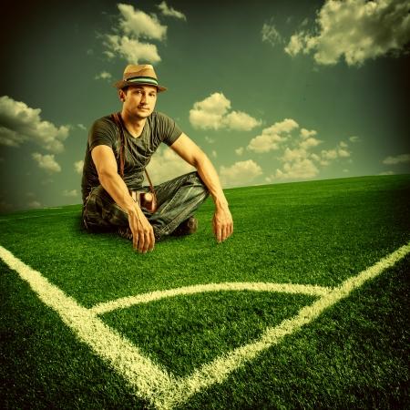Vintage uitzicht over Europese toeristische een voetbalfan met een camera zit op groen gras voetbalveld