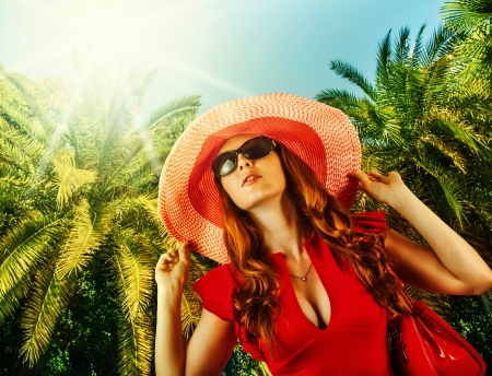 Young beautiful woman in red fashion dress, big hat and sun glasses on tropical resort