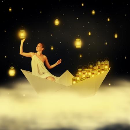 若いセクシーな女性の女神の紙の船で雲に浮かぶと夜空の星をぶら下げ