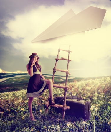 コンセプト - 旅行について夢を見ています。紙飛行機は雲の中に、はしごの近くに立ってのスーツケースを持つ美しい女性 写真素材