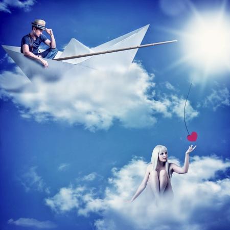 Jonge verliefde paar. Jonge knappe man zit in een boot en visserij - het aas van een mooie vrouw vangen Stockfoto