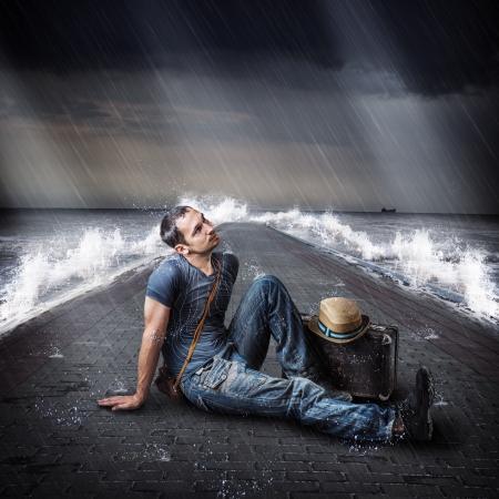 uomo sotto la pioggia: Giovane viaggiatore maschio è sul molo del mare durante una tempesta e la pioggia con una valigia in mano