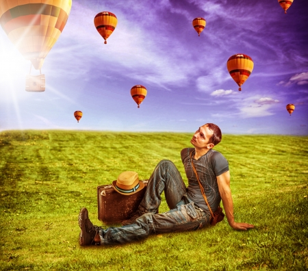 flying man: Young man traveler sitting on a fresh green grass and lookig to a flying balloons in blue sky