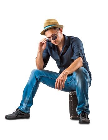 Jonge knappe man reiziger zittend op zijn koffer. Geïsoleerd op witte achtergrond Stockfoto