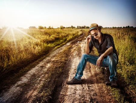 Young handsome man traveler sitting on his suitcase on a dirt road outdoor photo