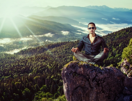 ravine: Young fashion man in dark blue shirt and gray pants sitting isolated on mountains stone